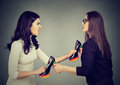 Women fighting tearing pulling apart shoes Royalty Free Stock Photo