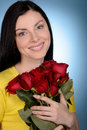 Women with flowers portrait of beautiful middle aged women hold woman holding a bunch red roses while isolated on blue Royalty Free Stock Image