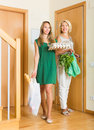 Women with food purchases at threshold two happy in bags focus on girl Royalty Free Stock Photo