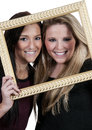 Women in a frame beautiful best friends looking through picture Stock Photos