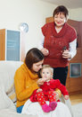 Women giving medicament to baby young mother with mature grandmother unwell at home Stock Photos
