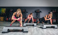 Women group training over steppers in aerobic hard class on a fitness center sport and health concept Royalty Free Stock Photo