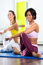 Women in the gym doing yoga exercise for fitness young and meditation better caucasian and latina people Stock Photography