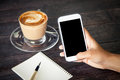 Women hand using smartphone cellphone tablet over wooden table with notebook and coffee cup Royalty Free Stock Photo