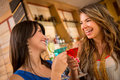 Women having at the bar two drinks looking very happy Stock Image