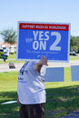 A women is holding a blue election vote sign to support medical marijuana voting signs it s about compassion yes on taken in Royalty Free Stock Image