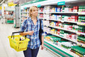 Women housewife with yellow basket shopping in dairy department supermarket Royalty Free Stock Photo