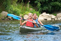 Women kayaking two smiling young down a river Stock Image