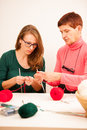 Women knitting with red wool. Eldery woman transfering her knowl Royalty Free Stock Photo