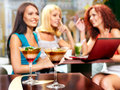 Women at laptop drinking cocktail in a cafe two sharpness on glass Stock Photography