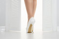 Women leg in white shoe looks out of the open door Royalty Free Stock Photo