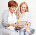 Women looking at photo frame mother with daughter happy smiling talking home Stock Photo