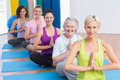 Women meditating with hands joined during fitness class portrait of happy fit Royalty Free Stock Images