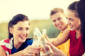 Women and men with drinks on the beach summer holidays vacation happy people concept group of friends having fun bottles of beer Royalty Free Stock Photo
