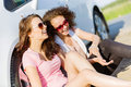 Women near car young pretty sitting white at side of road Royalty Free Stock Images