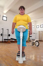 Women with overweight on scales in gym standing the Stock Images