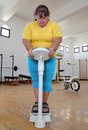 Women with overweight on scales in gym standing the Stock Photography
