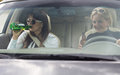 Women partying and drinking while driving two attractive along in a car view through the front windscreen Stock Photo