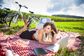 Women picnic and computer on grass in summer Royalty Free Stock Photos