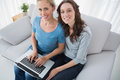 Women posing while surfing the web and sitting on sofa Stock Photo