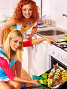 Women prepare fish in oven happy Royalty Free Stock Images