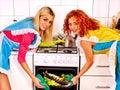 Women prepare fish in oven happy together Stock Photo