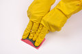 Women protecting hand with rubber glove from detergents as they use cleaning sponge on white background Royalty Free Stock Photography