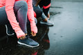 Women ready for running and training under the rain urban athletes lacing sport footwear over asphalt two getting outdoor Royalty Free Stock Images