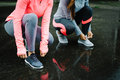 Women ready for running and training under the rain urban athletes lacing sport footwear over asphalt two getting outdoor Royalty Free Stock Photos