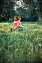 Women relaxing in park two young on field or meadow trees background Stock Photos