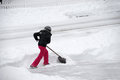 Women removing snow on the driveway by shovel after blizzard Royalty Free Stock Photo