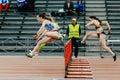 women running race in 100 meter hurdles