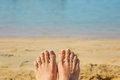 Women's feet in the sand against beach and sea Royalty Free Stock Photo