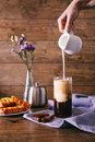 Women`s hand with creamer pouring milk in glass with coffee. Cinnamon sticks, homemade cookies and bunch of wildflowers Royalty Free Stock Photo