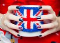 Women s hands keeping the cup with british symbol flag Stock Photography