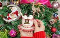 Women`s hands in a red wool sweater holding a mug with a snowman and marshmallow on the background of the Christmas tree.