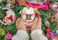 Women`s hands in a wool sweater holding a mug with a snowman and marshmallow on the background of the Christmas tree.