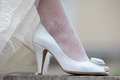 Women s shoes and hem of wedding dress leg of the bride in a white shoe Stock Images