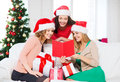 Women in santa helper hats with card and gifts christmas x mas winter happiness concept three smiling many gift boxes Royalty Free Stock Image