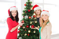 Women in santa helper hats decorating a tree christmas x mas winter happiness concept three smiling christmas Royalty Free Stock Photos