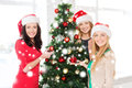 Women in santa helper hats decorating a tree christmas x mas winter happiness concept three smiling christmas Stock Photography