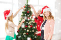 Women in santa helper hats decorating a tree christmas x mas winter happiness concept three smiling christmas Stock Image
