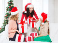Women in santa helper hats with many gift boxes christmas x mas winter happiness concept three smiling Royalty Free Stock Images