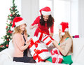 Women in santa helper hats with many gift boxes christmas x mas winter happiness concept three smiling Royalty Free Stock Photo