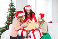Women in santa helper hats with many gift boxes christmas x mas winter happiness concept three smiling Stock Photography