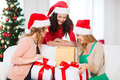 Women in santa helper hats with many gift boxes christmas x mas winter happiness concept three smiling Royalty Free Stock Image