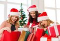 Women in santa helper hats with shopping bags sale gifts christmas x mas concept smiling and many gift boxes Stock Photo