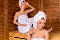 Women in sauna two attractive wrapped towel relaxing and keeping eyes closed Stock Photo
