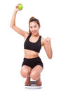 Women on scale cheering for achieving her weight loss goal