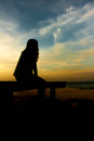 Women silhouette near sea sitting on bridge with twilight sky Stock Photos